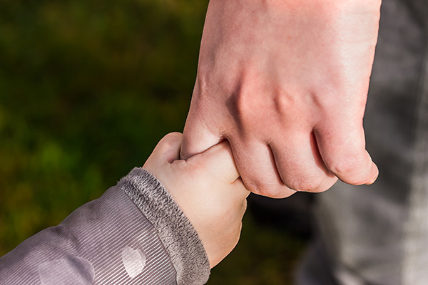 Father holding hands with daughter